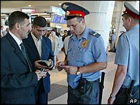 A police officer checks travellers' papers at Moscow's Domodedovo airport