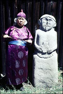 Siberian shaman Kenin-Lopsan poses with an ancestral gravesite figure
