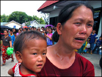 An ethnic Hmong refugee woman is overcome with emotion as she watches a family member being detained, Wednesday, Aug. 25, 2004