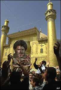 Supporters of radical cleric Moqtada Sadr hoist up his picture at the Imam Ali shrine on 23 August