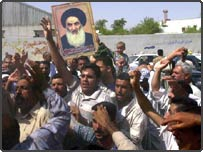 Shiite faithful hoist a picture of Grand Ayatollah Ali Sistani