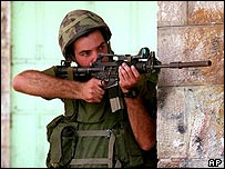 An Israeli soldier points an M-16 with a rubber bullet attachment at Palestinian demonstrators [archive photo]