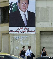 Lebanese walk in front of Lahoud poster