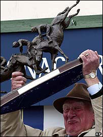 Ginger McCain holds the Grand National prize aloft