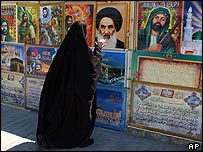 Iraqi Shia woman looks at picture of Sistani along with other Shia images