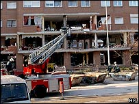 Firefighters work at the scene of the apartment block explosion, 4 April