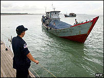 Malaysian marine policeman watches a boat on the Malaccan Strait