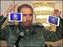 Fidel Castro holds up pictures of his alleged assassination plotters