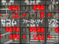 Tokyo pedestrians reflected in a stock price board showing strong gains