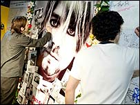 Fans of Kurt Cobain sign posters of the dead singer in Virgin Megastore