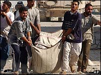 Iraqi men carry bodies of members of the Mehdi Army who were killed during the three-week crisis in the southern Iraqi city of Najaf