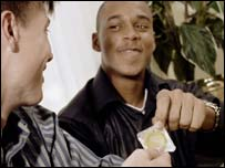Young men holding a condom