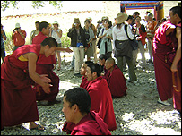 Monks with tourists in Sera monastery