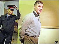 A Moscow policeman escorts Igor Sutyagin (right) to a courtroom in September 2002