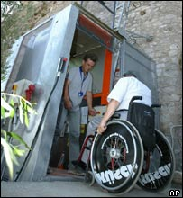 Spyros Stavrianopoulos, President of the Hellenic Paralympic Committee in a wheelchair tries the newly inagurated elevator to the ancient Acropolis hill, in Athens Thursday Aug. 12, 2004