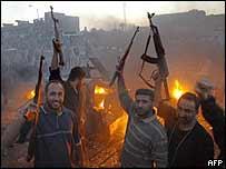 Mr Sadr's Army of Mehdi militia celebrate near a burning US Humvee in Baghdad