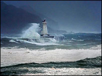 Waves breaking against a lighthouse (AP)