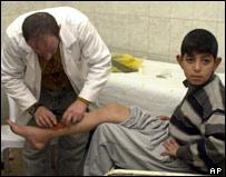 An Iraqi doctor treats an injured boy