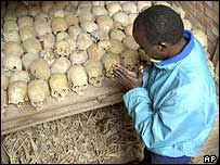 A survivor of the 1994 genocide prays over the bones of genocide victims at a mass grave in Nyamata