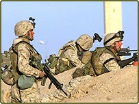 US Marines with the 2nd Battalion 1st Marine Regiment take cover during a gun battle with the Iraqi insurgents outskirts of Falluja, Iraq