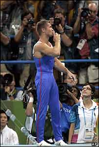 Russia's gymnast Alexei Nemov tries to quiet the crowd angry with low marking given for his high bar routine during the finals
