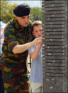 A Belgian soldier and the son of one of the 10 Belgian servicemen killed in the genocide look closely at a monument.