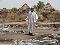 Un sudanés muestra su hogar destruido.