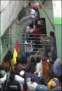 A woman is evacuated from Garcia Moreno prison on 17 February 2004