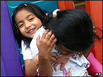 Two young girls tease each other as they make their way down a slide at the Alexandra Child Care Center in Singapore Thursday, Aug. 19, 2004