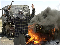 Iraqi insurgent raises his gun as coalition truck burns behind him