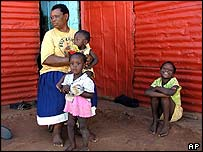 Mary Ramkani with her grandchildren Forgiveness, front, Agnus, right, and Happiness, back, outside her shack in the Lawley squatter settlement