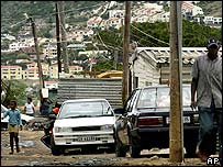 Squatters make their way through a muddy street in the Imizamo Yethu squatter settlement, against a backdrop of expensive housing, in Hout Bay, near Cape Town, South Africa