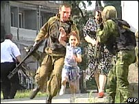 Child and mother evacuated by Russian special police forces troops (Image grab from Russian NTV channel)