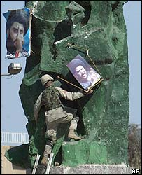 A US soldier removes posters of Moqtada Sadr from a statue in Firdus Square