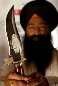 A Sikh priest displays a traditional kirpan