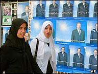 Women walk past Algerian election posters, April 2004