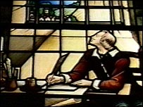 Stained glass window of John Bunyan in jail