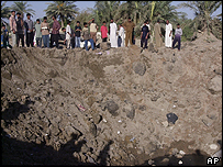 Iraqis view the crater believed to have been created by a US air strike 