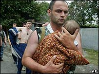 A soldier carries a baby after some women and children are freed from the school in south Russia