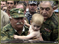 Russian soldier carries child to safety