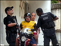 Policeman searches residents of Rio's Rocinha slum
