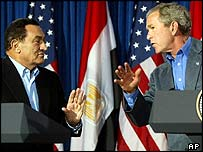 President Bush (R) leans over to talk to Egyptian President Hosni Mubarak (L)