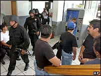 Federal police take over a station in Morelos while local officers look on