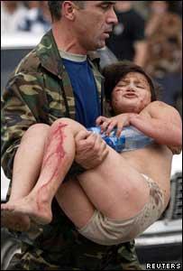 Hombre carga a una mujer herida.