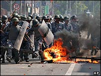 Police crash through a burning barricade during protests on Monday
