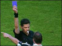 Referee holding blue card