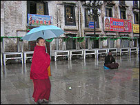 An itinerant monk begs for alms in the rain, as a young monk walks past