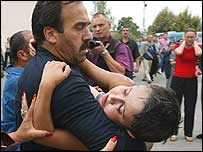 A child being carried out of the siege