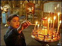 A boy lights a candle in the Holy Mother Of Kazan Cathedral in Moscow