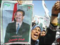 Palestinian holds a picture of Saddam Hussein during a protest against the US-led invasion of Iraq